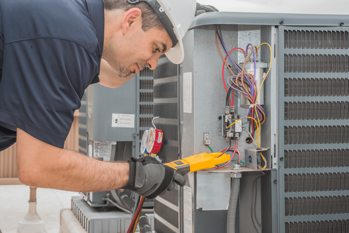 Certified HVAC technition in Texas inspects an air conditioning unit.