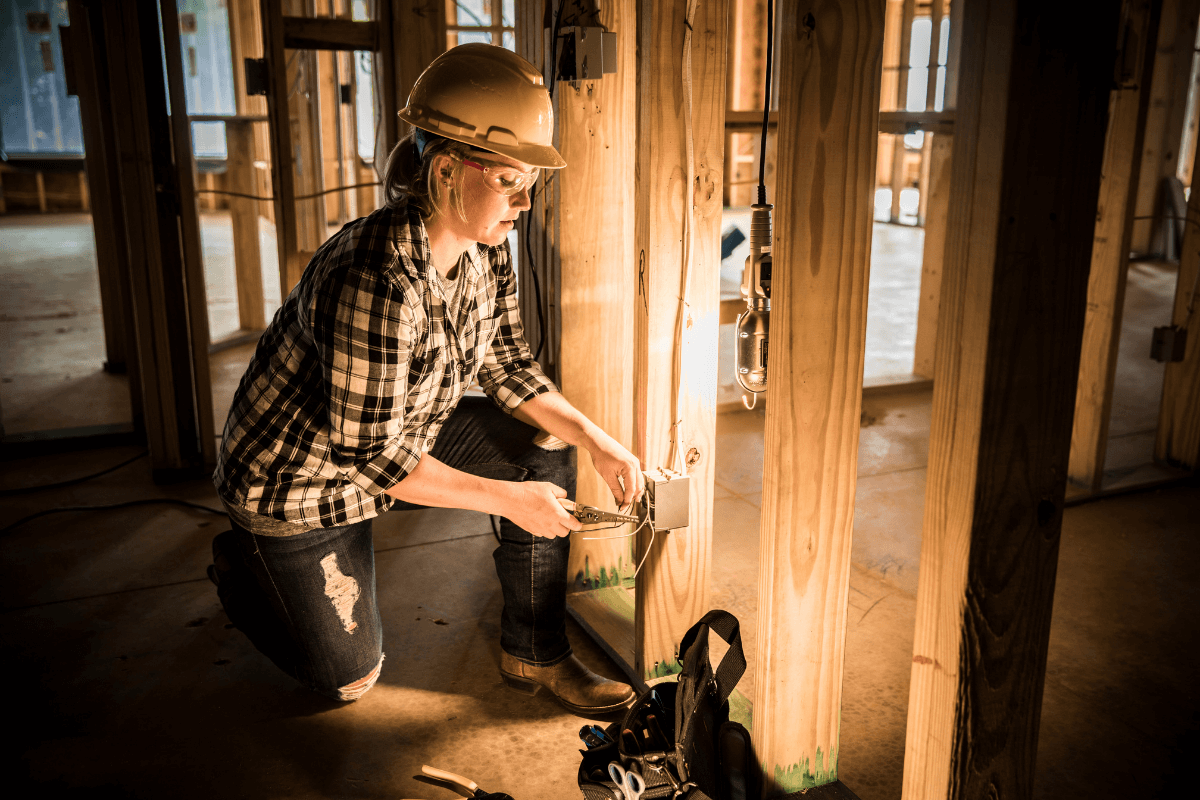 Female electrical technician installs a electrical outlet in a new build house.