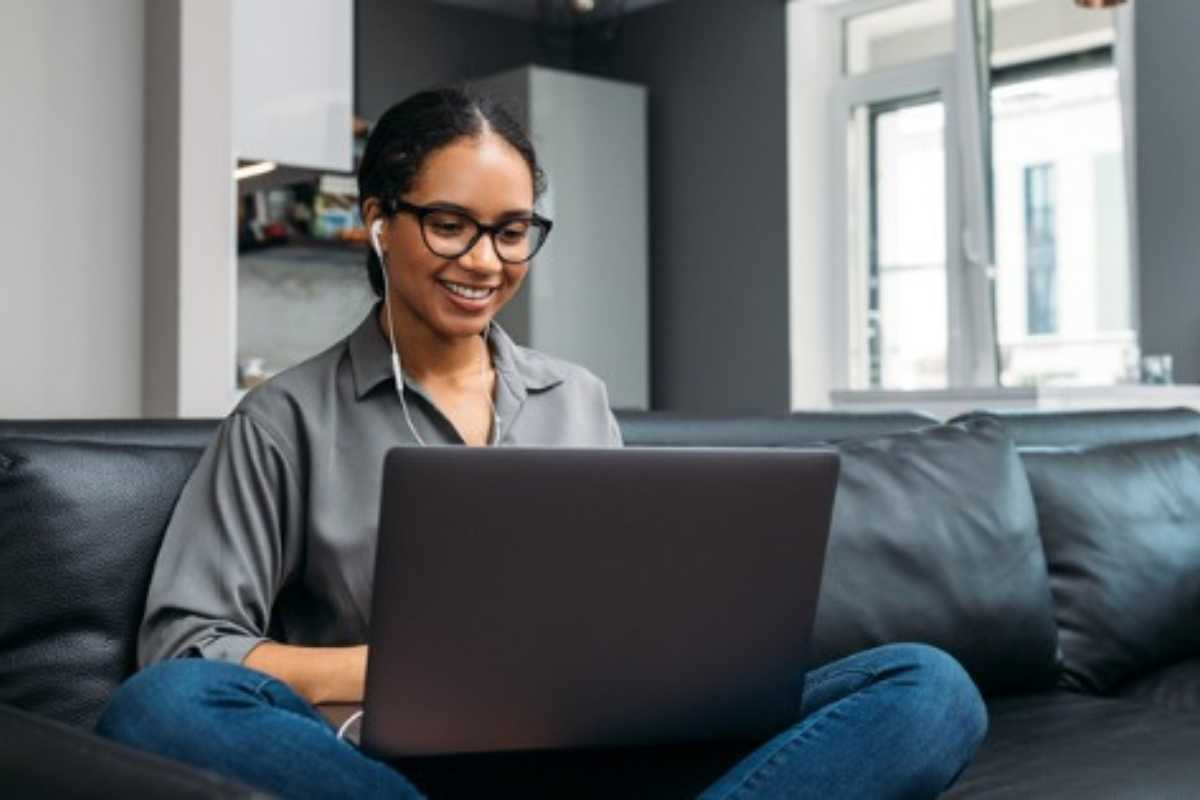 Woman sitting on the couch with her laptop taking the SCI career assessment tool
